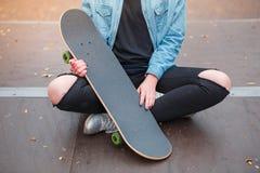 女孩在冰鞋公园拿着在她的胳膊的一个滑板 图库摄影