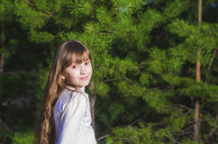 女孩在冷杉背景站立  免版税库存图片