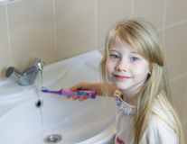 女孩在刷她的牙以后洗涤一把电牙刷 免版税库存照片