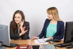 女孩在办公室谈话在电话要求同事等待 库存照片