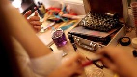 女孩在化妆师的艺术沙龙坐,并且她做着时兴的构成 股票录像