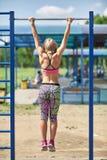 女孩在单杠拉扯了在运动场的公园 库存照片