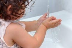 女孩在卫生间洗涤的手上 卷曲甜婴孩戏剧在水中 健康,儿童的卫生学概念 免版税库存图片