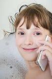 女孩在卫生间用电话叫 库存照片