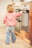 女孩在危险中从热的烤箱在厨房里 库存照片