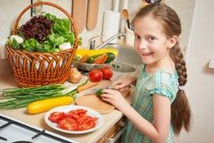 女孩在厨房、菜和新鲜水果里的砍黄瓜在篮子,健康营养概念 免版税库存照片
