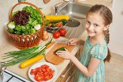 女孩在厨房、菜和新鲜水果里的砍黄瓜在篮子,健康营养概念 免版税库存图片