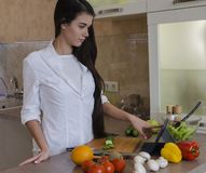 女孩在厨房里,烹调 库存照片