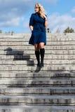 女孩在台阶的蓝色外套的 免版税库存图片