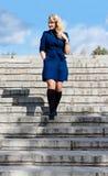 女孩在台阶的蓝色外套的 免版税图库摄影