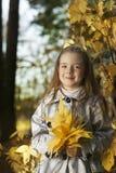 女孩在叶子秋天 免版税图库摄影