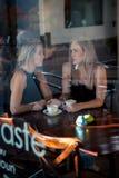 女孩在咖啡店的窗口里坐了 免版税库存照片