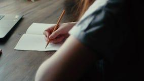 女孩在咖啡馆在有铅笔关闭的一个笔记本坐并且画 股票录像