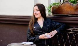 女孩在咖啡馆热奶咖啡杯子放松 在咖啡馆的早餐时间 女孩享用早晨咖啡 妇女户外饮料咖啡 库存照片