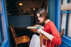 女孩在咖啡馆的一张桌上 免版税库存图片