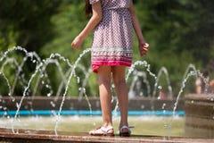 女孩在喷泉附近走 图库摄影