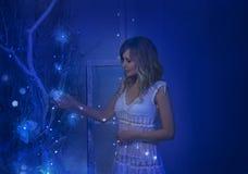 女孩在圣诞夜醒了,并且在她的屋子里被转动的奇迹,魔术把她变成一位神仙的公主 图库摄影