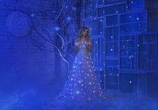 女孩在圣诞夜醒了,并且在她的屋子里被转动的奇迹,魔术把她变成一位神仙的公主 免版税库存图片