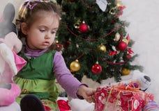 女孩在圣诞树下 库存照片