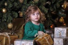 女孩在圣诞树下 免版税库存照片