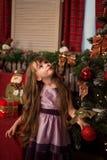 女孩在圣诞树和查寻附近站立 库存图片