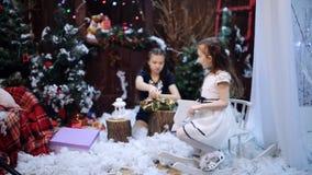 女孩在圣诞树孙女附近骑一匹木马包装一件白色披肩作为礼物对他们心爱 影视素材