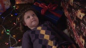 女孩在圣诞树附近说谎,看并且微笑 影视素材