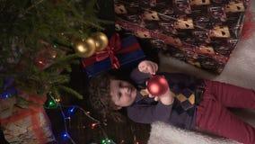 女孩在圣诞树附近说谎,看并且微笑 股票视频