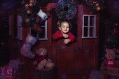 女孩在圣诞节玩具房子里 免版税库存照片