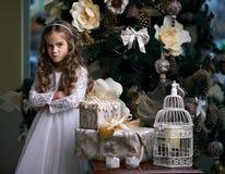 女孩在圣诞节礼物附近做鬼脸 库存图片