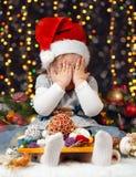 女孩在圣诞节装饰与礼物,黑暗的背景与照明和boke的皮面孔点燃,寒假概念 免版税库存照片