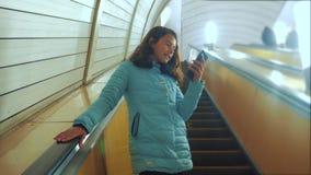 女孩在地下地铁的少年生活方式在自动扶梯乘坐,拿着智能手机 女孩深色的女儿 股票视频