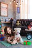女孩在地板上说谎在拥抱狗,微笑和摆在为的格子花呢披肩 库存图片