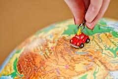 女孩在地球滚动一辆小的玩具汽车 免版税库存照片