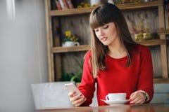 女孩在坐在咖啡馆的手机的读的SMS 库存图片