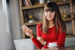 女孩在坐在咖啡馆的手机的读的SMS 库存照片