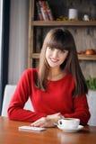 女孩在坐在咖啡馆的手机的读的SMS 免版税库存照片