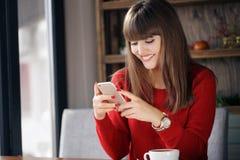 女孩在坐在咖啡馆的手机的读的SMS 免版税图库摄影