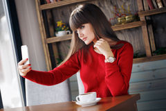 女孩在坐在咖啡馆的手机的读的SMS 免版税库存图片
