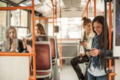 女孩在城市公共汽车使用一个手机 免版税库存照片