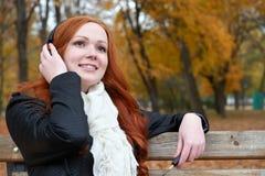 女孩在城市公园、秋天季节、黄色树和下落的叶子听在音频球员的音乐有耳机的,坐长凳 库存照片