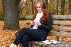 女孩在城市公园、秋天季节、黄色树和下落的叶子听在音频球员的音乐有耳机的,坐长凳 免版税图库摄影