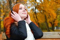 女孩在城市公园、秋天季节、黄色树和下落的叶子听在音频球员的音乐有耳机的,坐长凳 库存图片