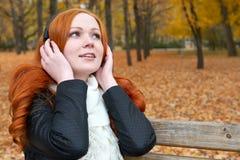 女孩在城市公园、秋天季节、黄色树和下落的叶子听在音频球员的音乐有耳机的,坐长凳 免版税库存图片