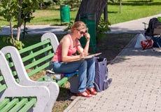 女孩在城市公园画坐一条长凳 免版税库存照片