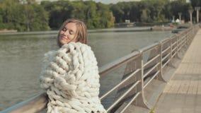 女孩在城市湖附近在早期的秋天走,包裹在美利奴绵羊的羊毛白色格子花呢披肩  股票录像