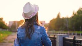 女孩在城市附近走并且为自然和视域照相在影片照相机 慢的行动 股票录像