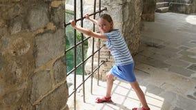 女孩在堡垒或城堡的震动格栅 她要出去 需要自由 女孩-大别墅的囚犯 股票录像