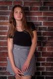 女孩在墙壁上站立 免版税图库摄影