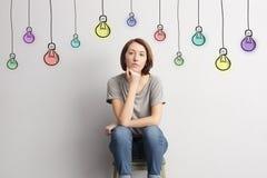 女孩在墙壁附近坐色的被画的电灯泡背景  免版税库存图片